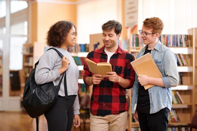 Gelukkige informele studenten met boeken die zich voorbereiden op seminar of examen en taken of vragen bespreken