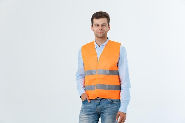 Gelukkige ingenieur glimlacht en staat vol vertrouwen, man met een caro-shirt en spijkerbroek met oranje vest, geïsoleerd op een witte achtergrond.