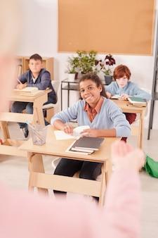 Gelukkige interculturele studenten van de middelbare school in vrijetijdskleding die naar de leraar kijken en naar haar luisteren terwijl ze aan een bureau in een groot klaslokaal zitten