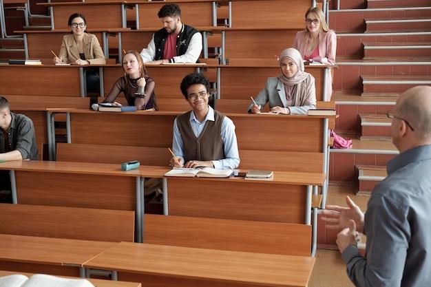 Gelukkige interculturele universiteitsstudenten zitten bij lange houten bureaus in de collegezaal, maken aantekeningen en luisteren naar de professor tijdens de les