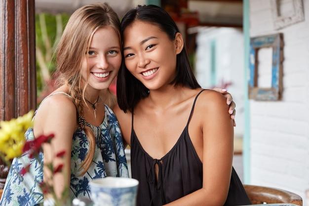 Gelukkige interraciale vriendinnen omhelzen elkaar en ontmoeten elkaar, drinken hete thee in een café, hebben een brede glimlach, zijn in een hoge geest, tonen echte vriendschap.