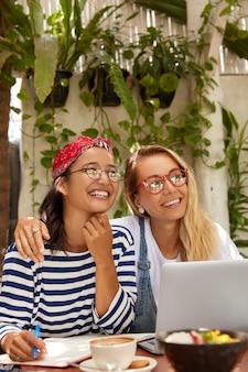 Gelukkige interraciale vrouwen omhelzen elkaar, zitten voor een geopende laptop, genieten van werk op afstand vanuit het café