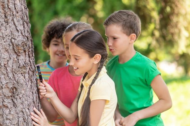 Gelukkige jeugd. geïnteresseerd uitziende meisjes en jongens met vergrootglas in de buurt van boom in park in de zomer