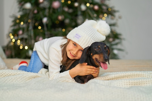 Gelukkige jeugd, kerst magisch sprookje. een klein meisje lacht met haar vriend, een teckelhond, bij de kerstboom.