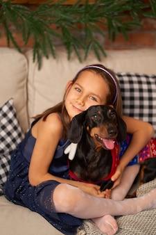 Gelukkige jeugd, kerstmagisch sprookje. een klein meisje lacht met de hond van haar vriendentekkel