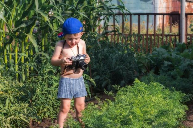 Gelukkige jeugd. kleine baby houdt een camera vast en probeert de foto in de tuin te maken. kleine fotograaf.