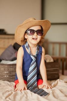 Gelukkige jeugd. leuk meisje dat op een manier speelt en grote cowboyhoed en zonnebril draagt. aanbiddelijk kind dat pret heeft binnen.