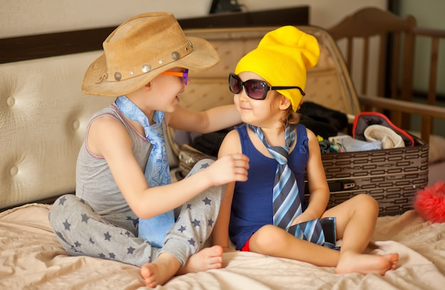 Gelukkige jeugd. leuk meisje en jongen spelen in een mode en het dragen van een zonnebril, cowboyhoed. schattige kinderen plezier binnenshuis.