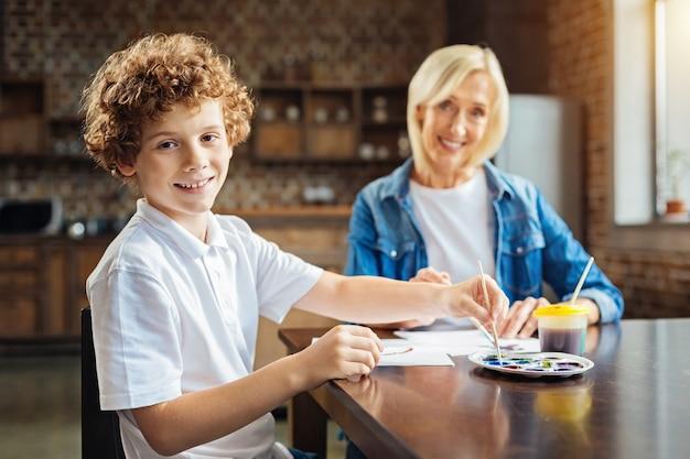 Gelukkige jeugd. selectieve aandacht voor een gelukkig ontspannen kind lachend voor de camera zittend aan een tafel en schilderen met zijn grootmoeder thuis samen.