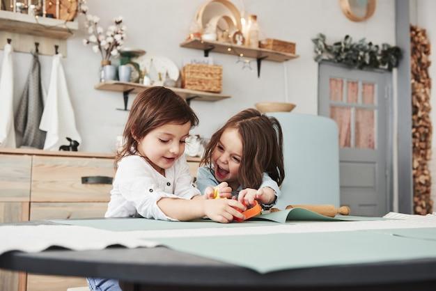 Gelukkige jeugd. twee kinderen spelen met geel en oranje speelgoed in de witte keuken.