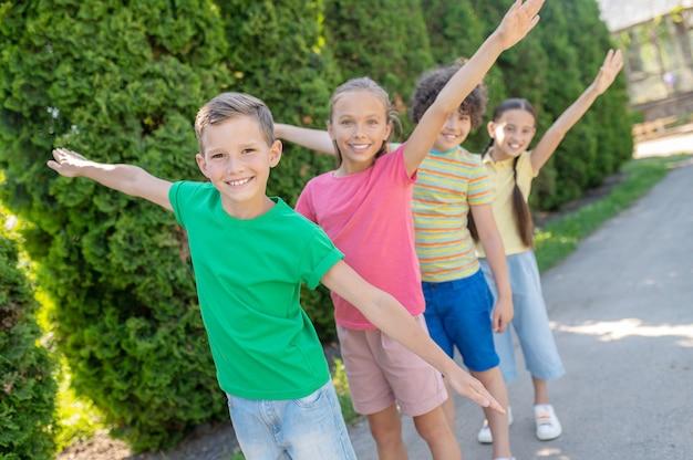 Gelukkige jeugd. vrolijk lachende jongens en meisjes met uitgestrekte armen naar de zijkanten spelen in het park op zomerdag
