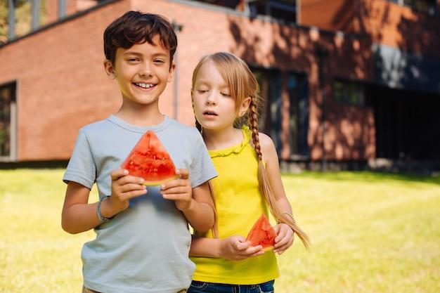 Gelukkige jeugd. vrolijke charmante kinderen glimlachen en eten een rijpe watermeloen