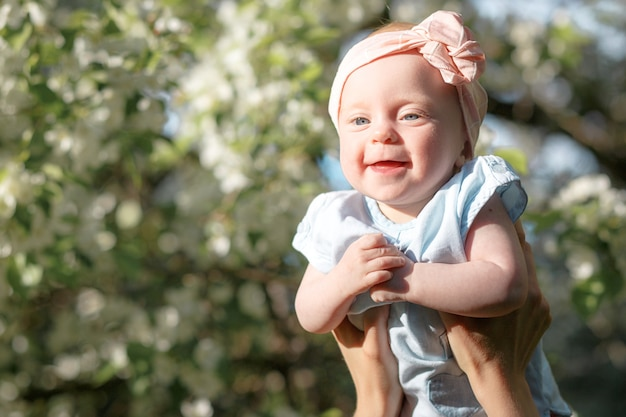 Gelukkige jeugd vrolijke moeder die zijn dochter opgooit en een klein meisje in de lucht gooit