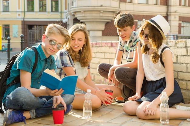 Gelukkige jeugdvrienden of middelbare scholieren hebben plezier, praten, lezen telefoon