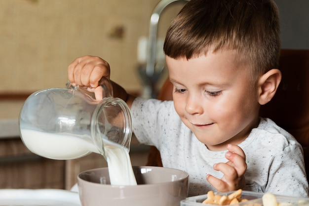 Gelukkige jong geitje gietende melk in een kom