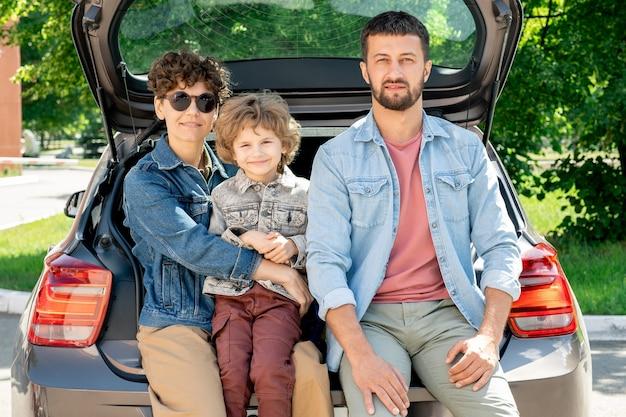 Gelukkige jonge aanhankelijke familie van vader, moeder en zoon van elementaire leeftijd zitten in de kofferbak op zonnige zomerdag