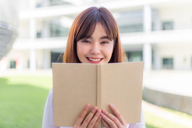 Gelukkige jonge aantrekkelijke aziatische vrouw leest graag haar boek buiten haar kantoorgebouw