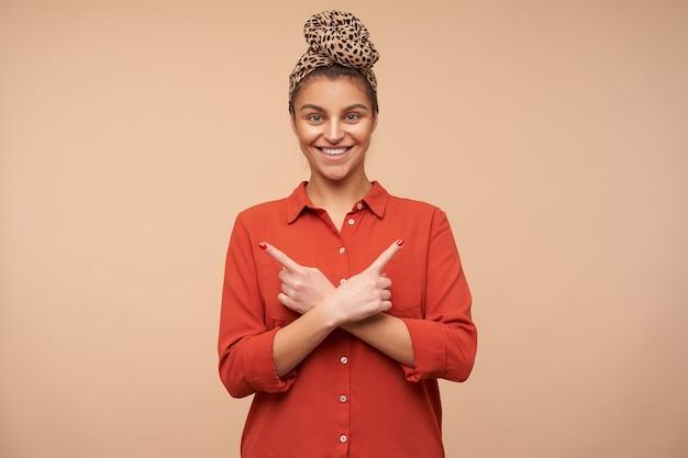 Gelukkige jonge aantrekkelijke donkerbruine vrouw die met hoofdband wijd glimlacht terwijl zij met wijsvingers in verschillende richtingen richt, die over beige muur wordt geïsoleerd
