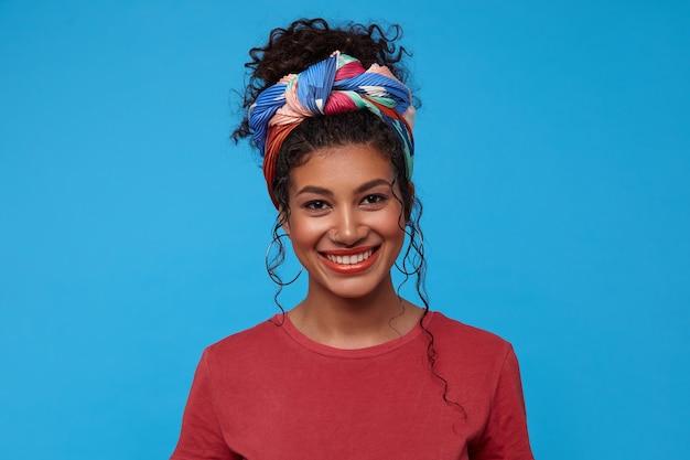 Gelukkige jonge aantrekkelijke donkerharige krullende vrouw met veelkleurige hoofdband die haar witte perfecte tanden laat zien terwijl ze vrolijk lacht, geïsoleerd over blauwe muur