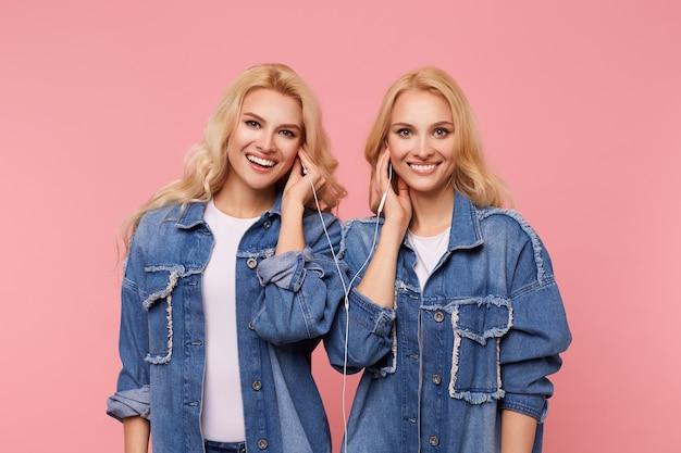 Gelukkige jonge aantrekkelijke langharige blonde zusters camera kijken met een charmante glimlach terwijl u luistert naar muziek in de koptelefoon, geïsoleerd op roze achtergrond