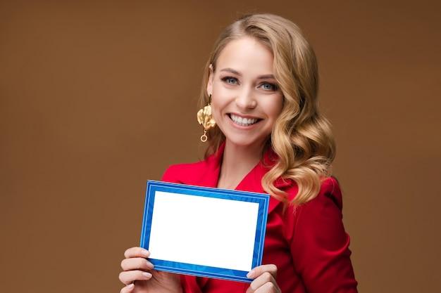 Gelukkige jonge aantrekkelijke vrouw die een mooie ansichtkaart vasthoudt terwijl ze naar de camera kijkt. geïsoleerd op bruine achtergrond. vakantie concept