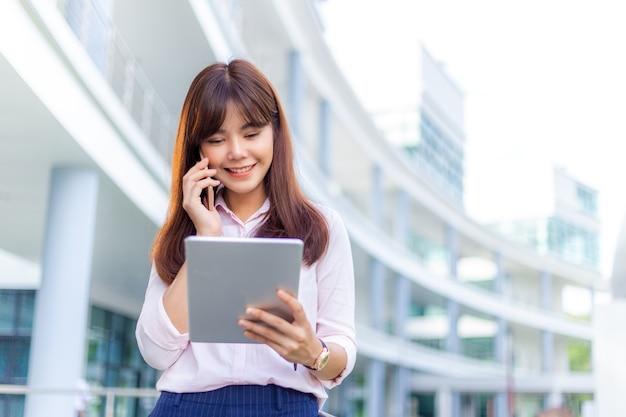 Gelukkige jonge aantrekkelijke zakenvrouw in haar roze shirt die op haar telefoon praat terwijl ze haar tablet gebruikt