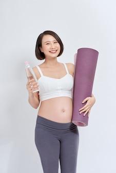 Gelukkige jonge actieve zwangere vrouw met een fles water en opgerolde mat die naar je kijkt met een glimlach terwijl ze op een witte achtergrond staat