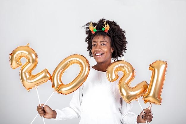 Gelukkige jonge afrikaanse amerikaanse vrouw die 2021 gouden kleurenballons houdt om te vieren
