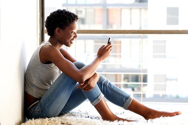 Gelukkige jonge afrikaanse amerikaanse vrouw die celtelefoon thuis door venster met behulp van