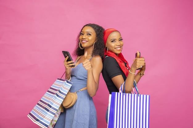 Gelukkige jonge afrikaanse dames poseren met boodschappentassen met duimen omhoog
