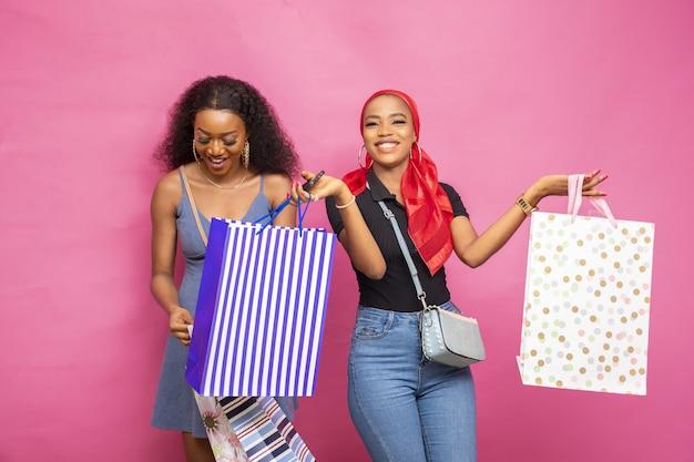 Gelukkige jonge afrikaanse dames poseren met boodschappentassen