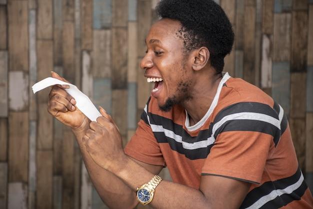 Gelukkige jonge afrikaanse man die naar een stuk papier kijkt