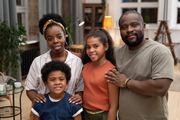 Gelukkige jonge afrikaanse man en vrouw en hun aanhankelijke zoon en dochter staan dicht bij elkaar voor de camera thuis