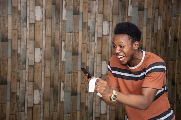 Gelukkige jonge afrikaanse man met een stuk papier