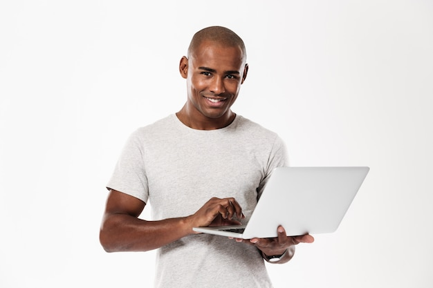 Gelukkige jonge afrikaanse mens die laptop computer met behulp van