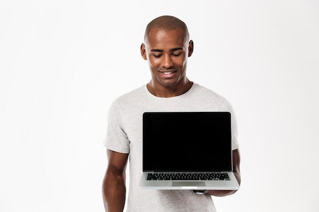 Gelukkige jonge afrikaanse mens die vertoning van laptop toont