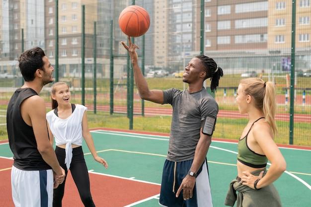 Gelukkige jonge afrikaanse sportman die bal op wijsvinger onder zijn verbaasde vrienden op basketbalspeelplaats houdt