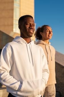 Gelukkige jonge afrikaanse sportman en zijn vriendin van kaukasische etniciteit in hoodies die zich tegen moderne architectuur en blauwe hemel bevinden
