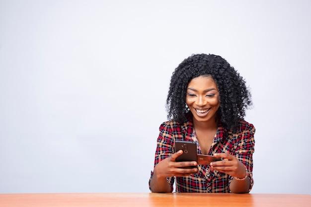 Gelukkige jonge afrikaanse vrouw die een creditcard en haar telefoon gebruikt