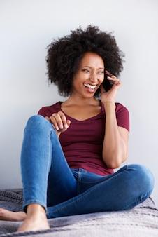 Gelukkige jonge afrikaanse vrouw die en op mobiele telefoon ontspant spreekt