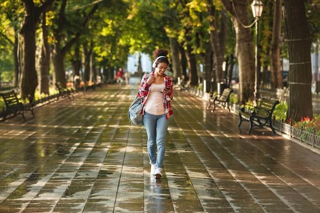 Gelukkige jonge afrikaanse vrouw die in openlucht in park loopt