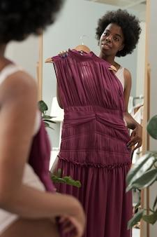 Gelukkige jonge afrikaanse vrouw die mooie jurk probeert