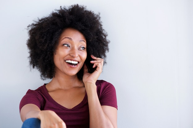 Gelukkige jonge afrikaanse vrouw die op celtelefoon spreekt