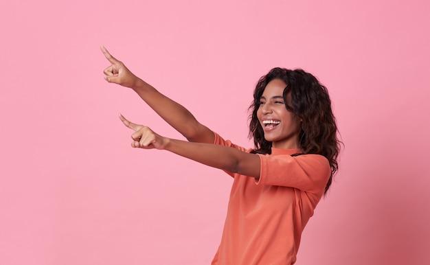 Gelukkige jonge afrikaanse vrouw die zich met haar vinger bevinden die over roze banner met exemplaarruimte richten.