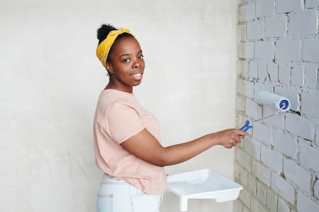 Gelukkige jonge afrikaanse vrouw met verfroller die in de hoek voor de bakstenen muur staat terwijl ze het in witte kleur schildert tijdens de renovatie van het huis