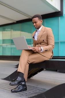 Gelukkige jonge afrikaanse zakenman met behulp van laptop zittend in de stad buiten