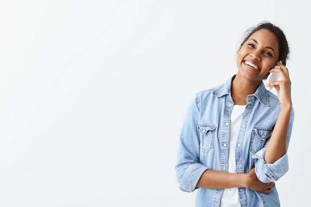 Gelukkige jonge afro-amerikaanse vrouw die in blauw overhemd met donker haar haar bespreking op smartphone bespreekt die opzij kijkt met charmante aantrekkelijke glimlach.