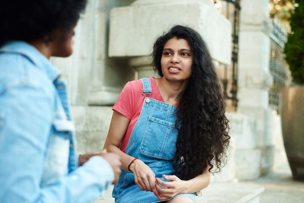 Gelukkige jonge afro-amerikaanse vrouw die lacht, geniet van een leuk gesprek met een indiase vriend, een tienermeisje met een gemengd ras dat lacht buiten concept.