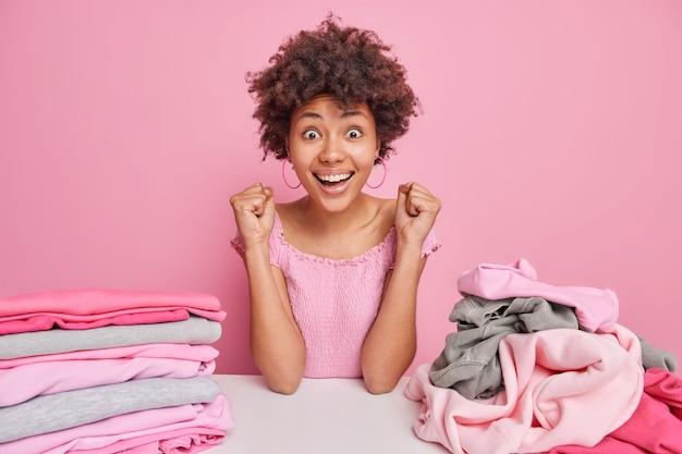 Gelukkige jonge afro-amerikaanse vrouw vouwt de was thuis poseert aan tafel met stapel gevouwen en gevouwen kleding balt vuisten van vreugde als bijna klaar huishoudelijk werk geïsoleerd over roze muur