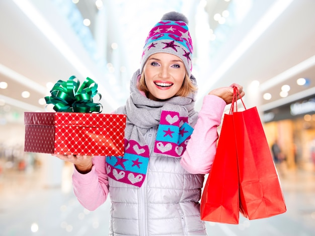 Gelukkige jonge amerikaanse vrouw met een kerstcadeau in een winter bovenkleding